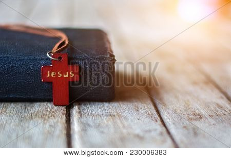 Closeup Brown Christian Cross Necklace Next To Holy Bible