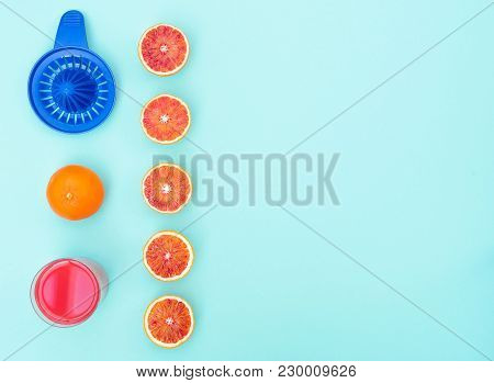 Glass With Fresh Made Blood Orange Juice On Vibrant Blue Background. Flat Lay Style With Copy Space.