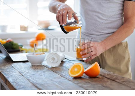Benefits From Fresh. Close Up Of Male Hands Pouring Orange Fresh Filled With Vitamins After Squeezin