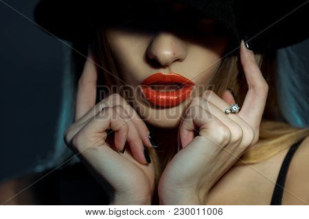 Horizontal Portrait Of Girl With Healthy Skin And Red Lips With Her Eyes In Shadow In Studio