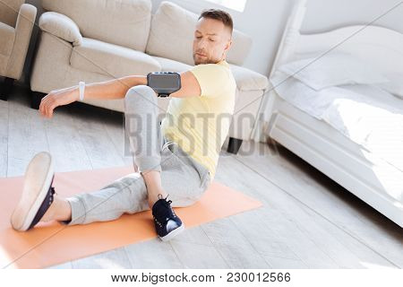 Warm Up Muscles. Vigorous Nice Enthusiastic Man Working Out While Sitting On Mat Board And Elongatin