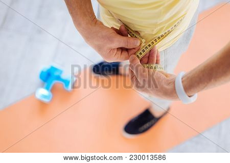 Improve Physical Health. Close Up Of Male Hands Using Metre Ruler While Man Standing On Mat Board