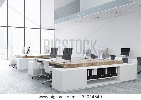 White Open Space Office Corner With White And Wooden Tables And Rows Of Computers On Them. A Two Flo