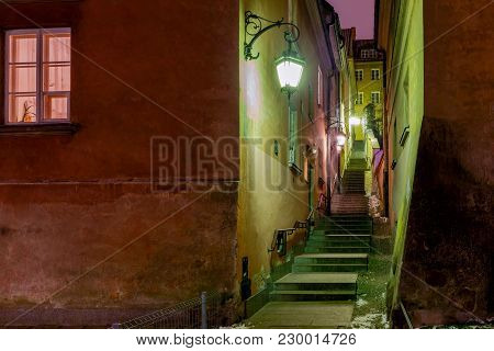 Old Medieval Narrow Street At Night In The Historic Center Of Warsaw. Poland.