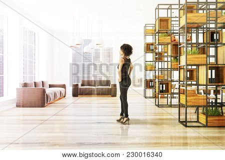 Ligth Wooden Wall Office Interior With A Wooden Floor A Black Bookcase And Two Gray Sofas. An Africa