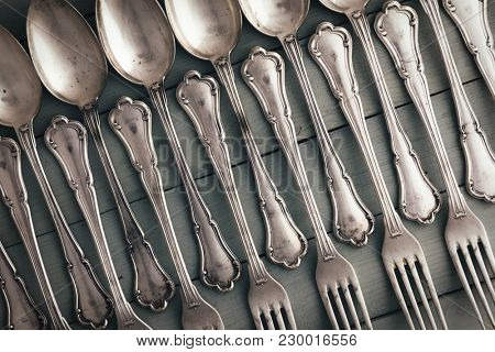 Set of antique silverware from spoons and forks on wooden table. Food concept background