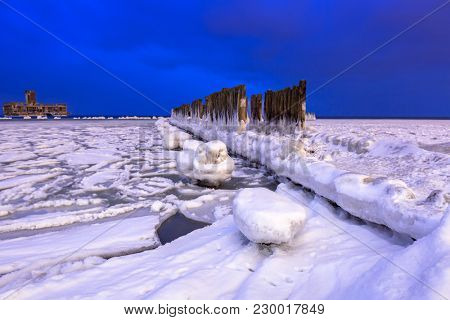 Frozen coastline of Baltic Sea in Gdynia at dusk, Poland