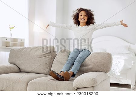 Perfect Day. Nice Exuberant Curly-haired Girl Smiling And Sitting On The Couch And Wearing A White S