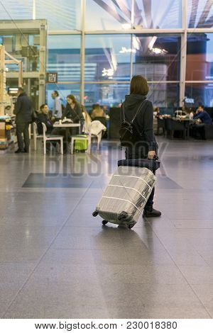 Woman With A Suitcase At The Airport. Protecting A Suitcase From Thieves