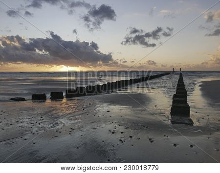 Sunset At The Beach With Bollards And Reflections On The Water