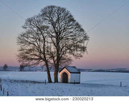 Small Chapel Next To A Tree At Sunrise And View Over Snowy Fields