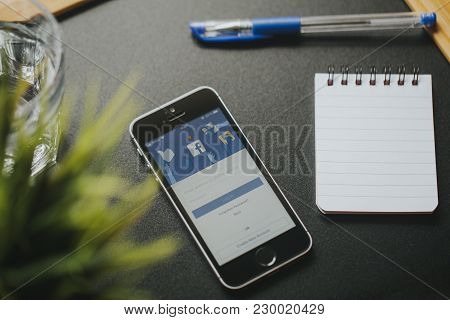 Malaga, Spain - March 6, 2018: Mobile Phone With Facebook App In The Screen, On A Black Desk Close T