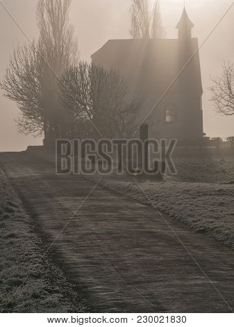 Chapel at sunrise on a hill on a misty morning