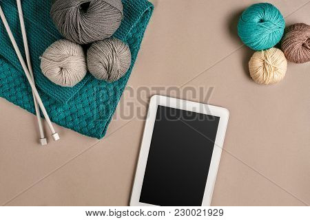 Grey And Turquoise Knitting Wool, Knitting Needles And A Tablet With A Black Screen On Beige Backgro