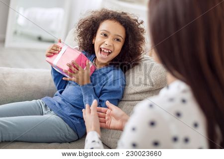 Being Overwhelmed. Nice Exuberant Curly-haired Girl Looking At Her Mother And Smiling And Holding He