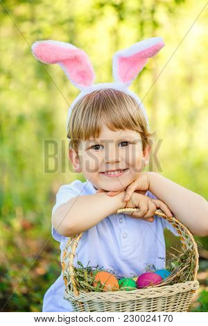Cute little child boy wearing bunny ears on Easter day in spring garden. Kid holding basket with painted eggs. Toddler boy in rabbit costume play outdoors in Easter Egg Hunt.