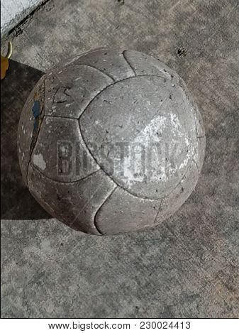Worn-out Soccer Ball On Concrete In The Sun