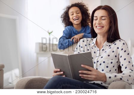 Laughter. Beautiful Exuberant Dark-haired Young Woman Laughing And Holding A Book And Her Daughter S