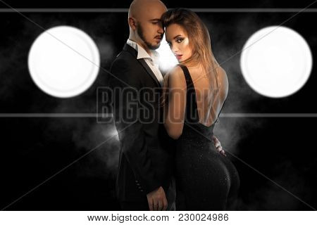 Glamour Young Couple In Black Suits Hugs In Studio On Black Background With Smoke