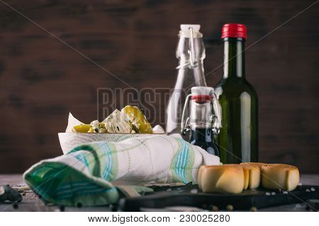 Bowl Full Of Green Stuffed Peppers On Dark Wooden Board With Few Glasses In Background