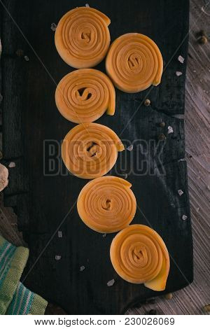 Top View On Six Rolls From Smoked Cheese On Dark Wooden Board