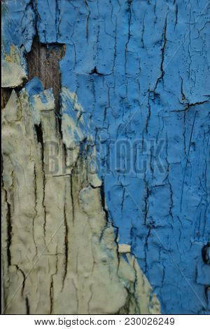 Blue And Yellow Peeling Paint On Old Wooden Wall