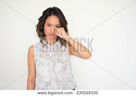 Portrait Of Upset Young Asian Woman Wearing Blouse Standing And Wiping Eye With Hand. Offense Concep