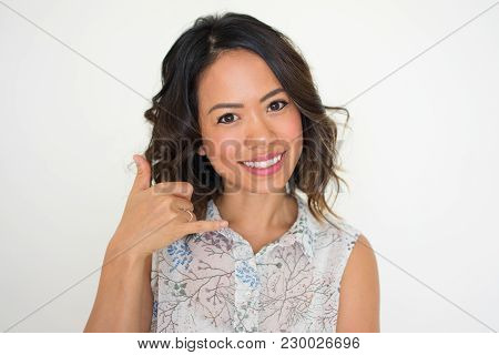 Portrait Of Young Asian Female Manager Showing Calling Gesture, Looking At Camera And Smiling. Conta