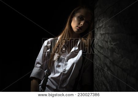 A Young Girl In A Shirt With Suspenders, Sad And Tired