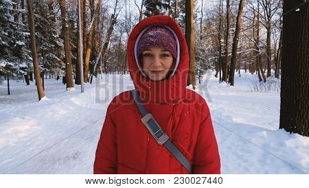 A Girl In A Red Down Jacket Walks And Looks Straight Into The Camera In The Woods In Winter At Sunse