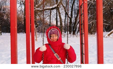 A Girl In A Red Down Jacket Swinging On A Red Swing At Sunset, Slow Motion