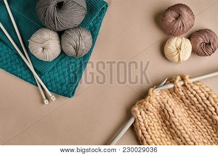 Grey And Brown Ball Wool And Knitting On Needles On Beige Background. Knitting As A Kind Of Needlewo