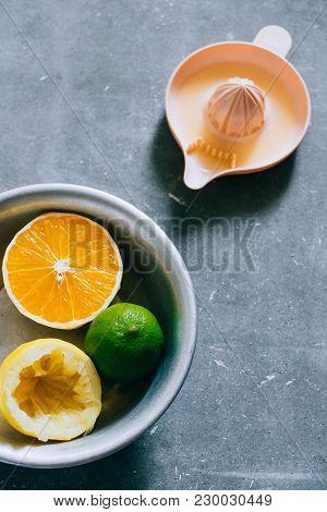 Lemons, Lime, Orange In A Metal Plate, A Citrus Juicer On A Gray Concrete Background. Make Fresh Lem