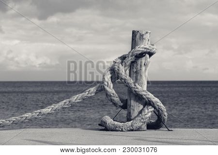 Old Rope On Seafront, Sea And Cloudy Sky. Black And White Toned Landscape.