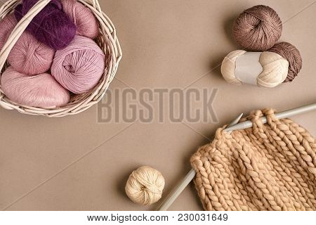 Pink And Brown Ball Wool And Knitting On Needles On Beige Background. Knitting As A Kind Of Needlewo