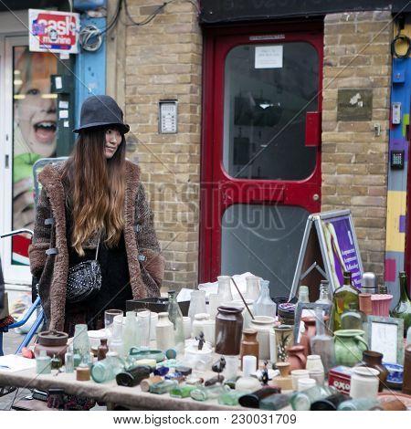 London, Uk - April 22, 2016: The Girl In A Stylish Hat Sells Vintage Glass Bottles On Brick Lane