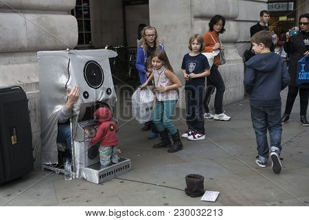 London, England - July 12, 2016 Street Children Watch An Actor Who Runs A Puppet At The Disco
