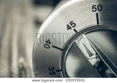 45 Minutes - Three-quartes Of An Hour - Macro Of An Analog Chrome Kitchen Timer On Wooden Table