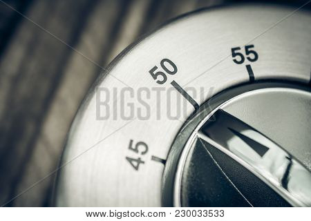 50 Minutes - Macro Of An Analog Chrome Kitchen Timer On Wooden Table