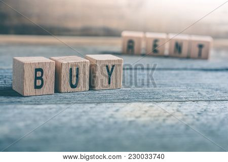 Macro Of The Words Buy And Rent Formed By Wooden Blocks On A Wooden Floor