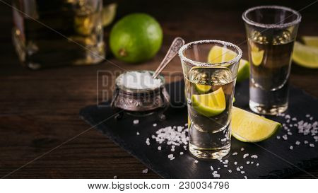 Gold Tequila Shot With Lime And Sea Salt On Black Table.