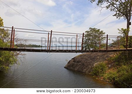 An Old Footbridge Over The Outlet From Sorabora Lake In A Scenic Sri Lanka Landscape