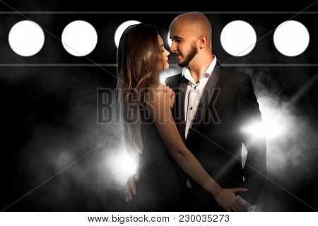 Glamour Young Sexy Couple In Black Suit And Dress Posing In Studio On Black Smoke Background With Li