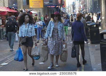 London, England - July 12, 2016 Two Brunette Girls Are Walking Along The Brick Lane