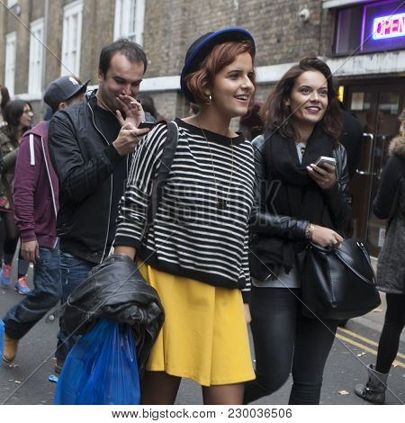 London, Uk - April 22, 2016: A Smiling Girl In A Striped Blouse, Yellow Skirt And A Small Hat Goes B