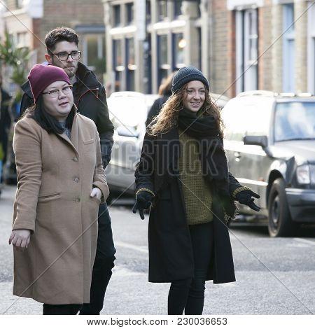 A Motley Crowd Walks Along The Brick Lane
