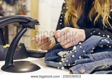 Girl Scanning Barcode From A Denim Jacket.