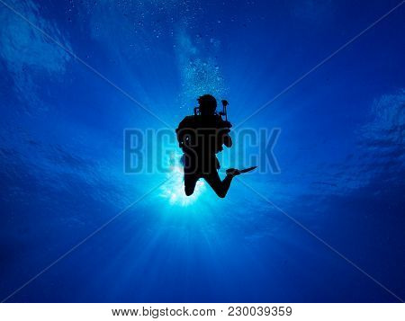 Silhouetted Female Diver With Sun And Blue Sky And Water