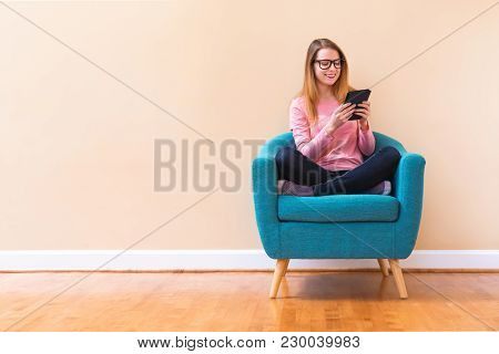 Young Woman Reading With An E-reader In A Large Interior Room