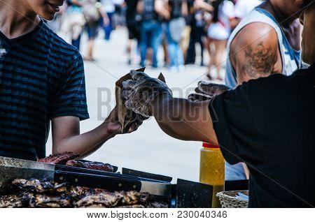 Hamburger Seller Handing A Hamburger To A Buyer